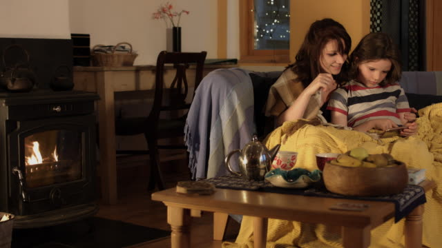 4k Shot in Warm and Cozy Atmosphere of Mom with Son playing near Fireplace video