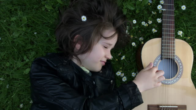 4k Shot of a Cute Child Outside Playing Guitar on the Grass video