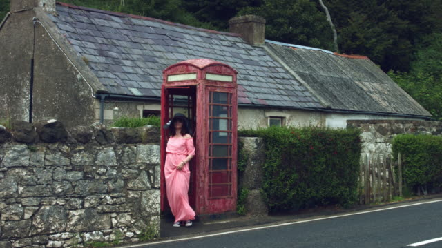 4k Shot of a Woman posing in a Red Telephone Box, United Kingdom video