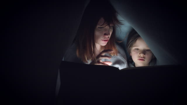 4k Shot of Child and Mom under Blanket Reading Horror Story Book video