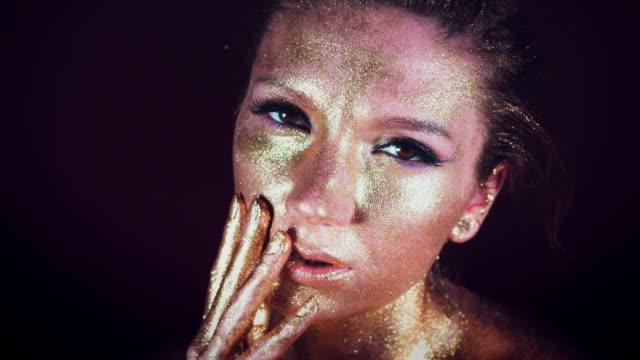 4k Studio Shot of a Golden Glittery Face Woman video