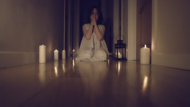 4k Thriller Shot in a Long Hall with Candles, Child Praying on Knees video
