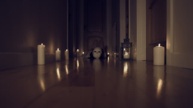 4k Thriller Shot in a Long Hall with Candles, Creature with Mask moving video