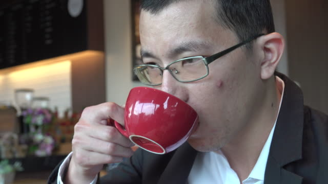 4k: Young Asian Man drinking coffee video