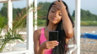 4K_Looking at camera and texting at the beach video