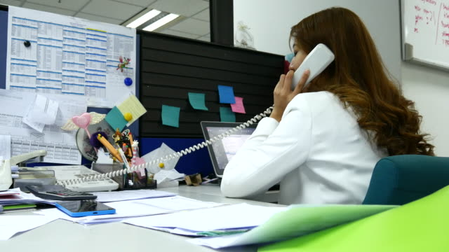 4K:Asian Businesswoman talking on a phone in her office video