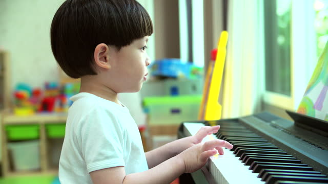4K:Asian little boy playing practicing the piano in his home. video