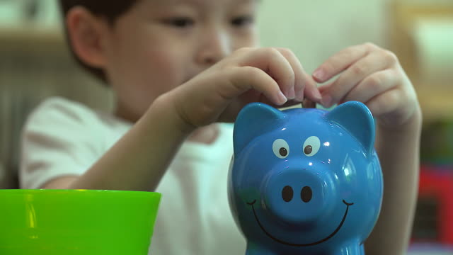 4K:Baby boy inserting a coin into a piggy bank, indoor financial concept. video
