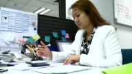4K:Businesswoman calculating in office video