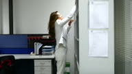4K:Businesswoman finding document from cabinet and reading video