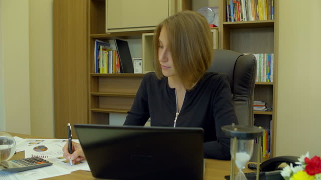 4K:Businesswoman working with laptop computer and calculator on the desk in her office. video