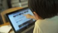 4K:Little boy using notebook touch screen. video