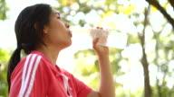 4K:Woman runner drinking water after race video