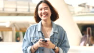 4K:Women smiling and using smart phone video