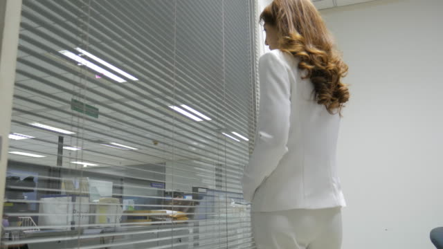 4K:Young Businesswoman looks through blinds out of her office video