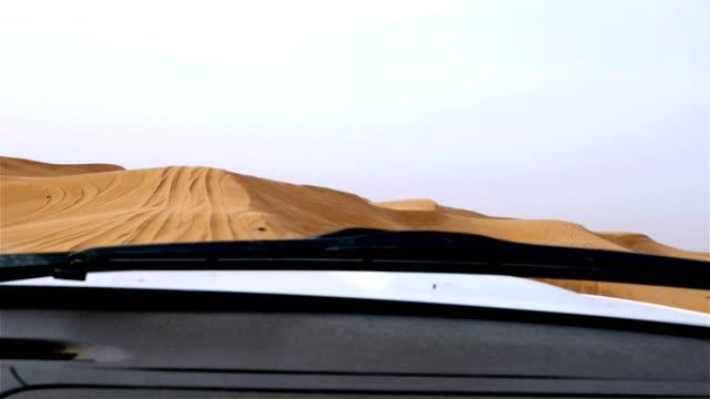 4x4 off road land vehicle taking tourists on desert dune bashing safari in Dubai, UAE video