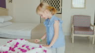 A 6-year-old girl enters the hotel room. On his bed sees a surprise from the hotel and room cleaner - a heart of towels and flower petals video