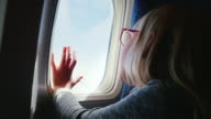 A 6-year-old girl with spectacles sits in a plane, looks out the window. Her hand is pressed to the porthole - a happy journey video