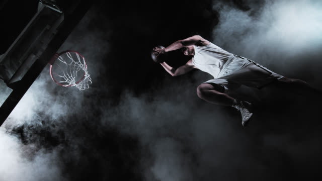 SLO MO of a basketball player performing a slam dunk video