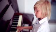 a blonde boy playing the piano video