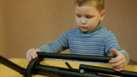 a boy collects design on the table and have success video