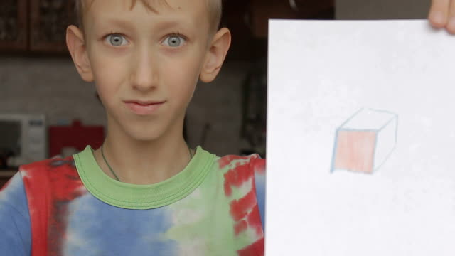 a boy shows the picture of a cube video