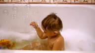 a child playing in the bath with soap bubbles video