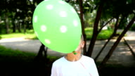 a child playing in the Park with balloon video