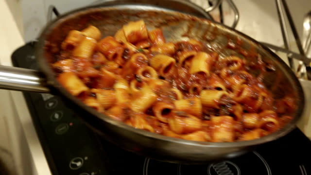 a cook that turns the cooking pan with pasta, sauce of tomatoes and eggplants video