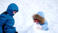 a happy children plays with snow in the park. buried in the snow video