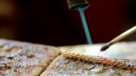 a jeweler behind a desk solder product. repair gold chain video
