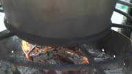 a large pot on the fire with mulled wine video