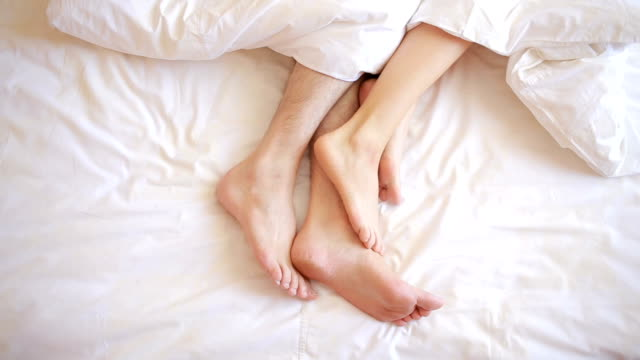 a man and a woman in bed. male and female legs top view, white linens video