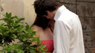 a man and a woman kissing and holding hands video