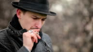 a man in a hat smokes video