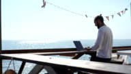 a man uses a laptop in a cafe on the waterfront video