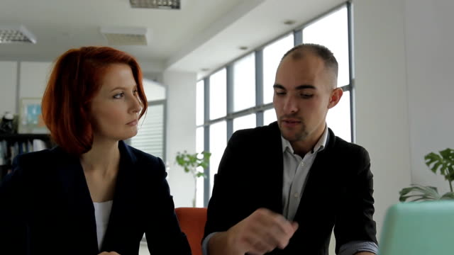 a middle-aged man businessman business manager talking with his client, woman in large, bright office video