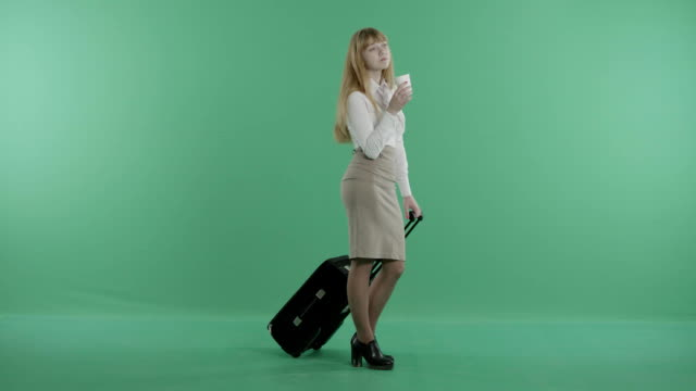 a redhead woman stands holding a coffee and a baggage in hands video