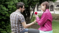a shy man gives a red rose to a beautiful woman - love - lover- fond - kiss video