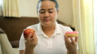 Fat woman selects a doughnut or apple video