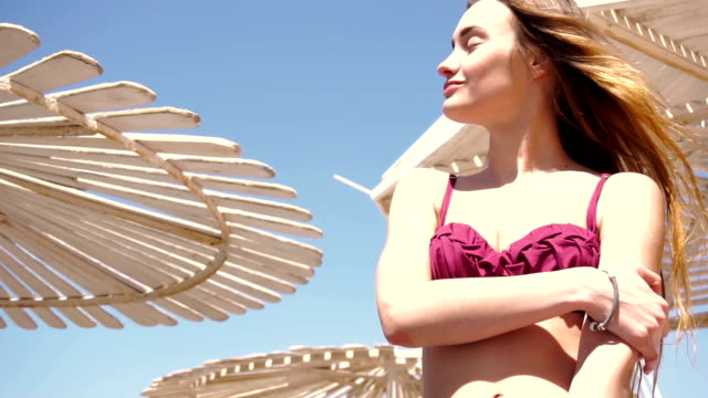 a young girl in a bathing suit with beautiful body stands on the beach in the wind near umbrellas and smiles video