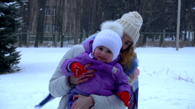 a young girl in a winter cap keeps the child in your arms video