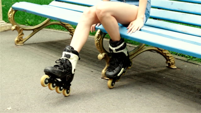 a young girl is sitting in a park in rollerblading video