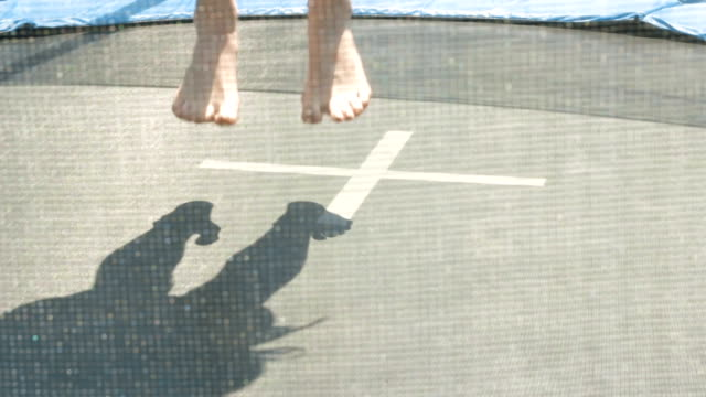 a young girl jumping on a trampoline in summer video