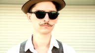 a young man with a mustache and hat yawns video