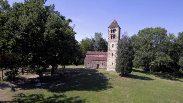 above view of isolated old catholic christian romanesque church with bell tower in nature outdoor scene  4k aerial drone orbit wide sho video