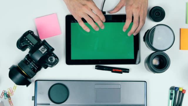 Above view. Photographer working wuth tablet at desk. Green screen video