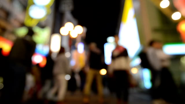 Abstract blurred background of Pedestrians walking on street and Night illumination of Namba Zone in Osaka, Japan video