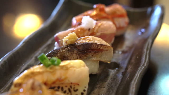 Aburi nigiri set or seared sushi set. Japanese food, raw fish with fast fire burn video