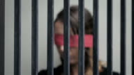 abused young woman imprisoned in a cell, blindfoldedwith red ribbon video